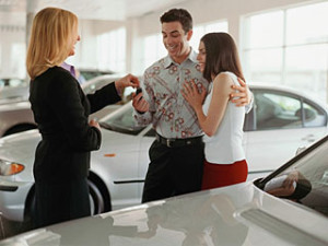 Saleswoman giving car keys to couple at car dealership